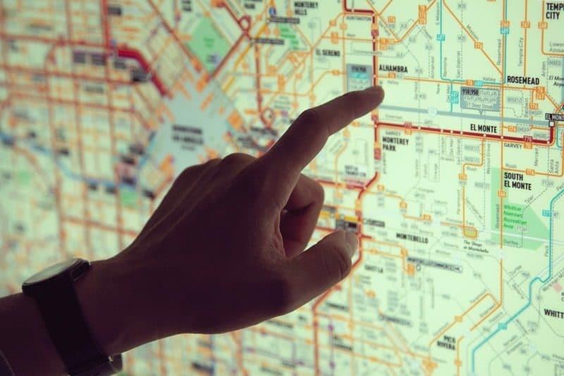 Main désignant un itinéraire sur une carte du métro - pour indiquer le chemin à suivre.