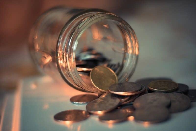 Tarro con monedas saliendo que representan el flujo de valor de negocio