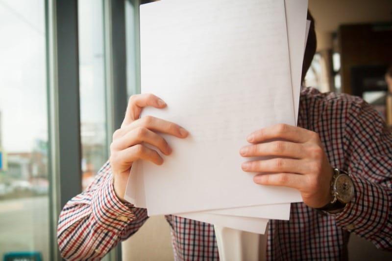 Une personne tient des documents dans ses mains (et se couvre le visage).
