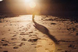 Huellas en la arena de una persona que camina a lo lejos