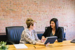 Dos mujeres en una mesa negociando o conversando lo que podría ser una contratación o discusión de aumento salarial