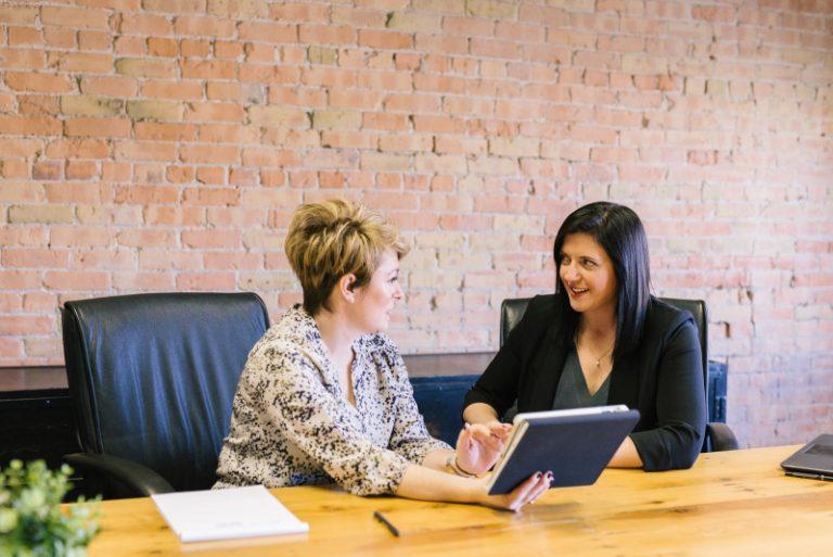 Zwei Frauen an einem Tisch, die über eine Einstellung oder eine Gehaltserhöhung verhandeln oder sprechen.