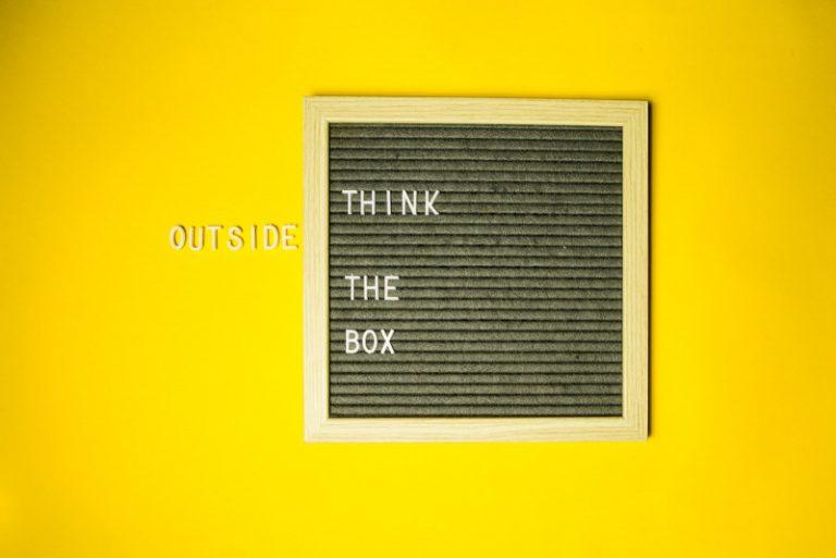 "Pared amarilla con letrero vintage que dice ""think out of the box"""