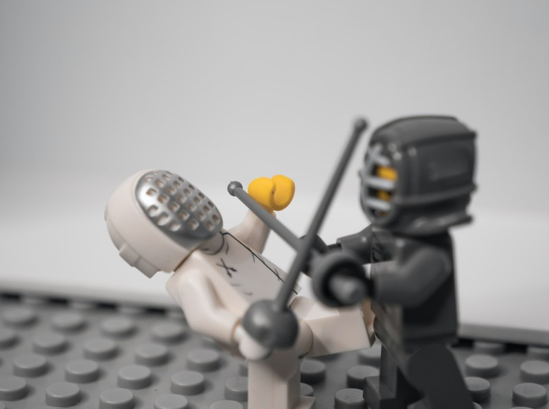 Zwei Lego-Fechtfiguren kämpfen in Anlehnung an den Kampf EDT gegen Backlog.