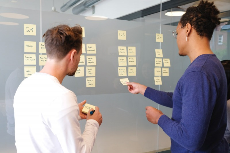 Two people talking in front of a kanban board.