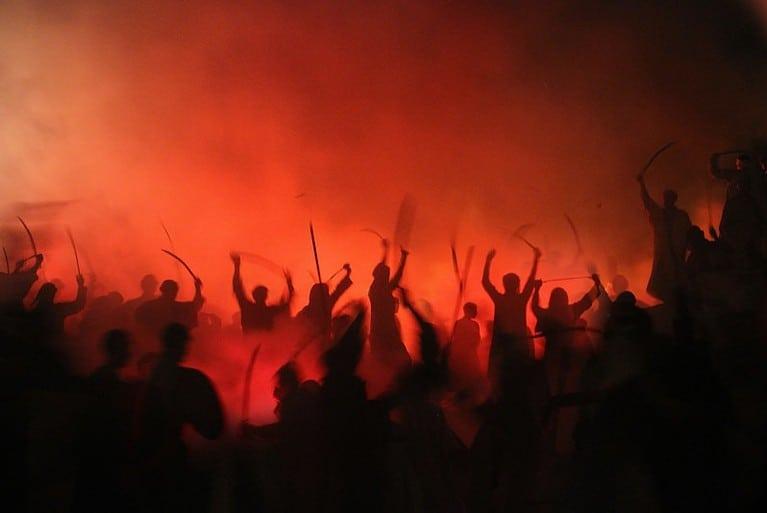 Sombras de gente reuniéndose durante la noche para una protesta